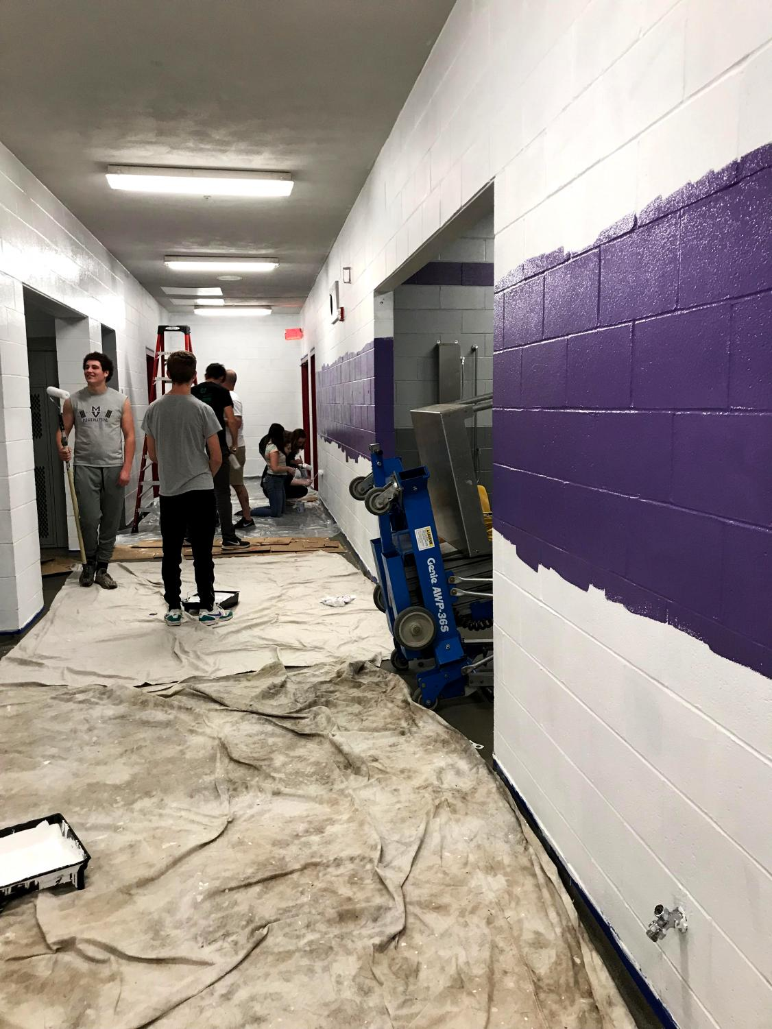 Leadership students paint the boys' locker room.