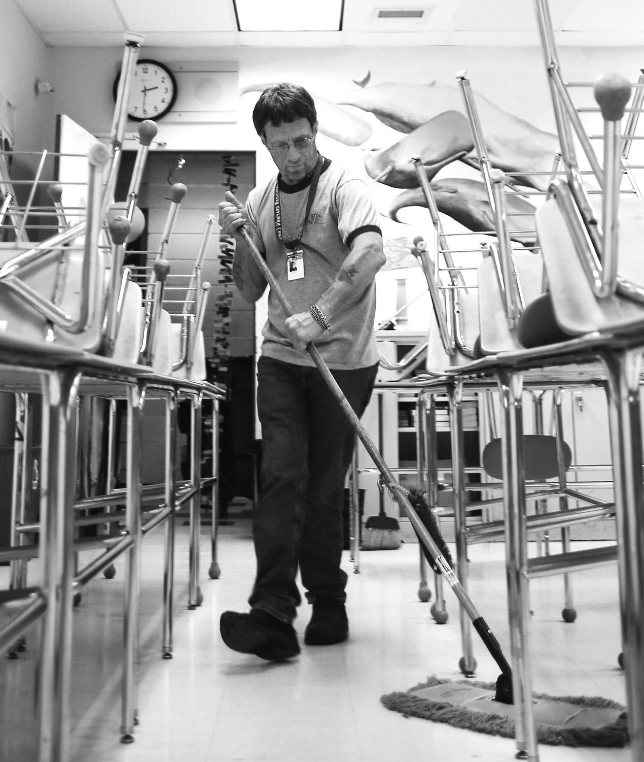 Custodian Leon Hawksley sweeps a classroom floor. during after school hours.