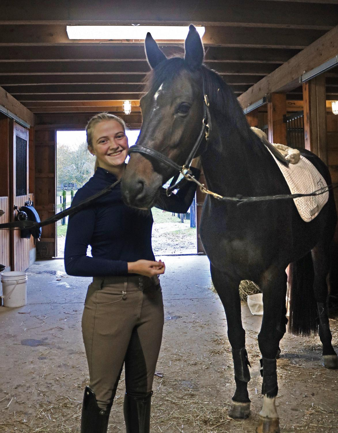 Junior Bella Thorpe stands alongside her horse and close companion, Bella Ymas, inside the stables of Woodbe Farm.