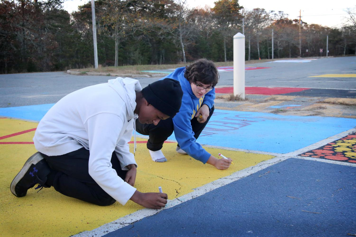 Senior Tripp Hopkins (left) and Skylar Hall add some finishing touches to the parking spots.