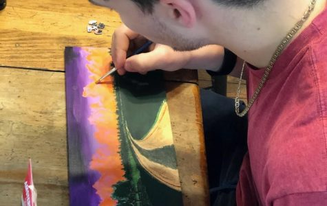 """Senior Kenny Hatt works on one of many paintings titled """"Cotton Candy Clouds"""" during his time in quarantine."""