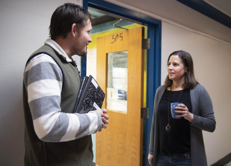 Mrs. Dingledy talks with English as a Second Language teacher Mr. Foley during passing time in the hallway.
