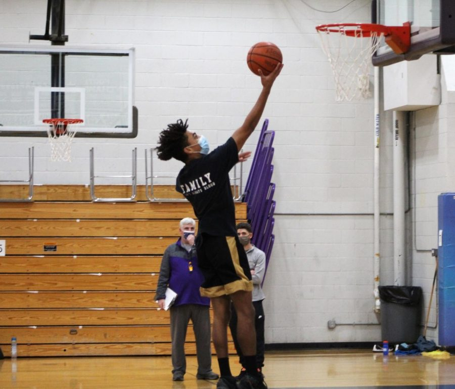Senior basketball captain Mike Trusty goes for a lay-up at tryouts on Monday night.